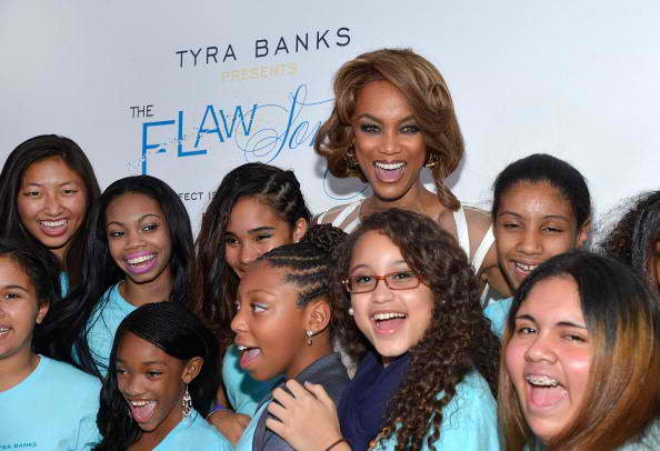 Tyra Banks (C) poses for pictures with girls from the TZONE foundation 2
