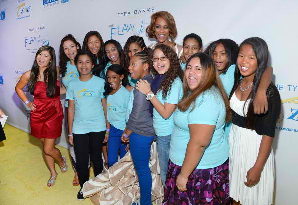 Tyra Banks (C) poses for pictures with girls from the TZONE foundation